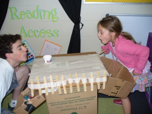 A second grade student can remind a Middle School student of the curiosity and wonder that can be found in everyday materials while they both construct cardboard arcade games that will later be played by Preschool students.